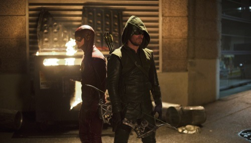 Grant Gustin as The Flash and Stephen Amell as The Arrow standing together in a street scene facing opposite directions