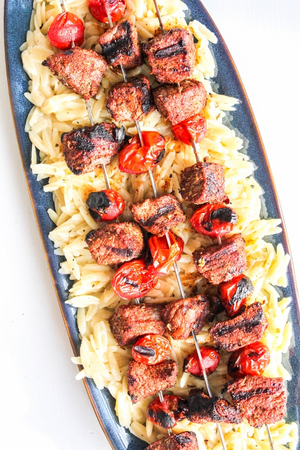 Flavorful cubes of sirloin steak and fresh tomatoes are grilled to perfection, then served atop a bed of creamy, lemony orzo. It's the perfect summer meal and best enjoyed al fresco!