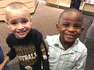 Photo of two little boys - one white the other black with matching haircuts and matching smiles