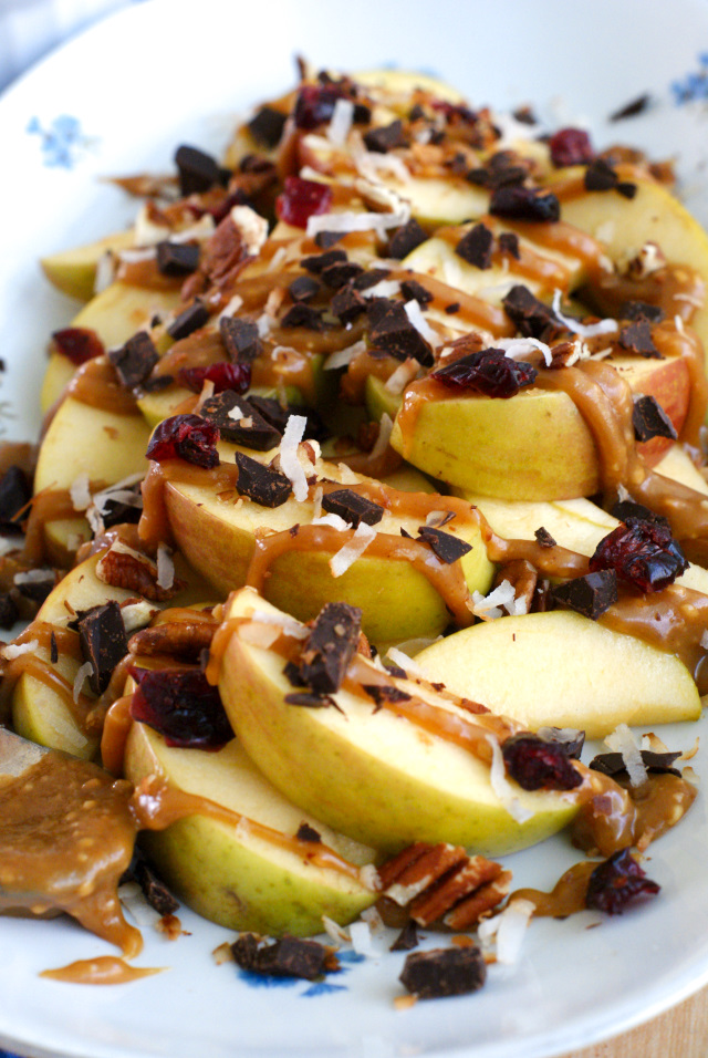 Apple Nachos are topped with chopped nuts, toasted coconut, dried cranberries, Lindt Chocolate, and a peanut butter maple sauce!  Yum!