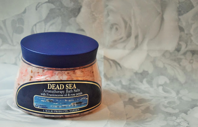 A clear tub with pink bath salts inside with a blue lid and blue label.