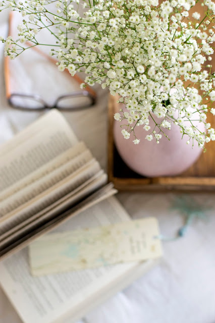 Book with glasses and flowers on white background