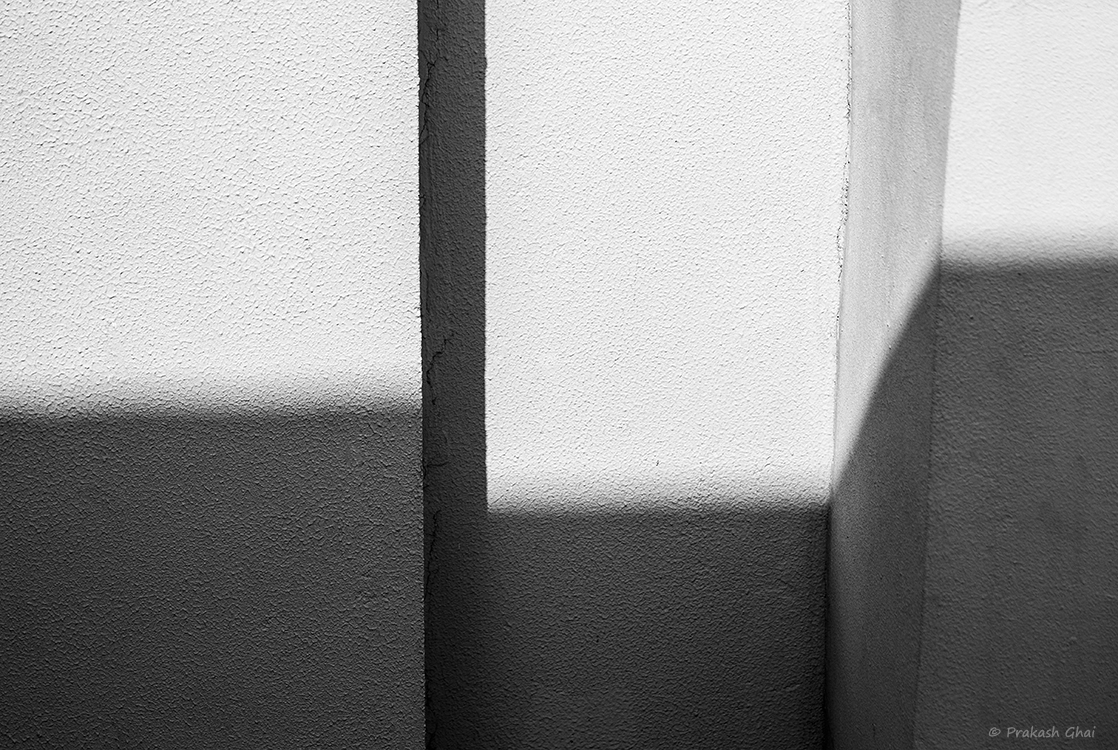 A Black and White Minimalist Photo of Light and Shadow contrast on a textured wall.