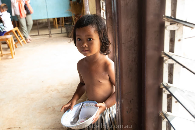 Small child, a girl around 3 years of age, hangs by the doorway hoping to sneak some lunch.