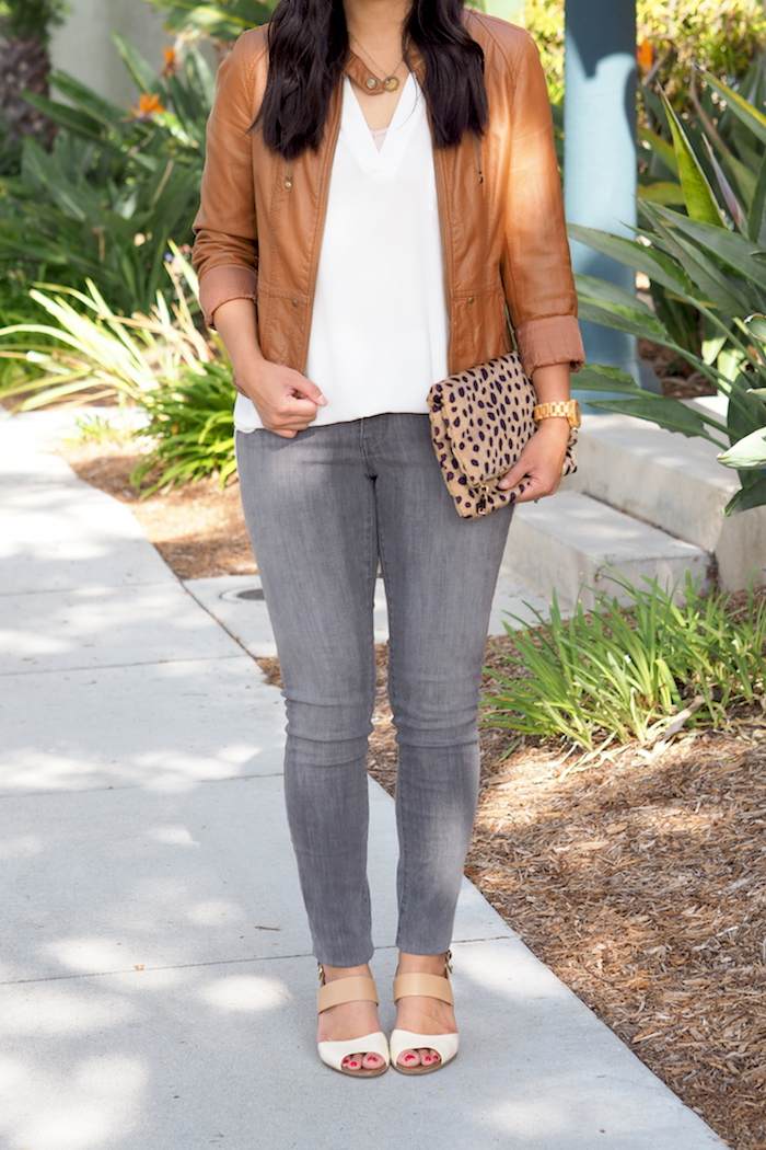 tan leather jacket + white blouse + grey jeans + leopard clutch
