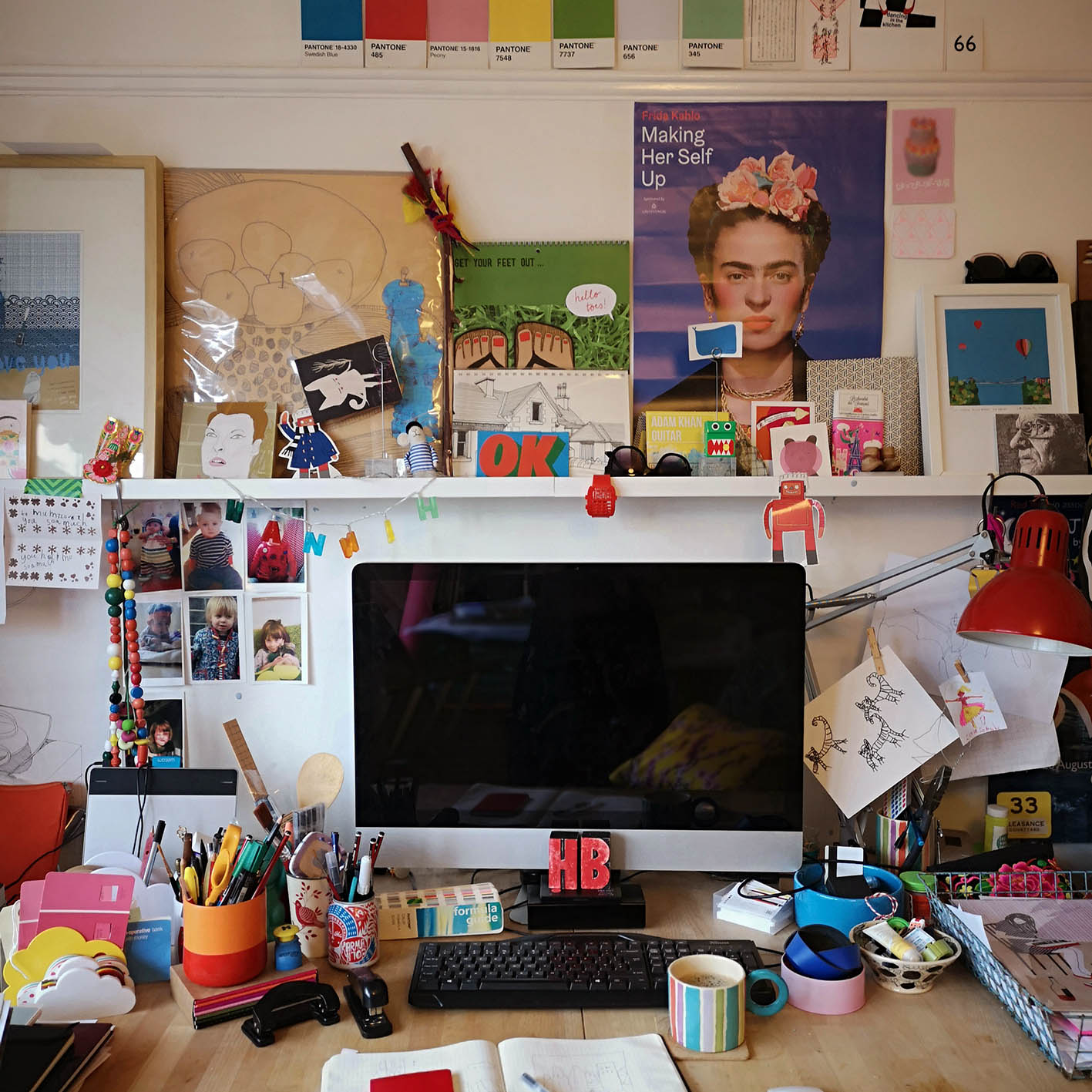 Behind Hannah's monitor is a plethora of colourful inspiration, as well pens, brushes, sketchbooks and other tools of the trade!