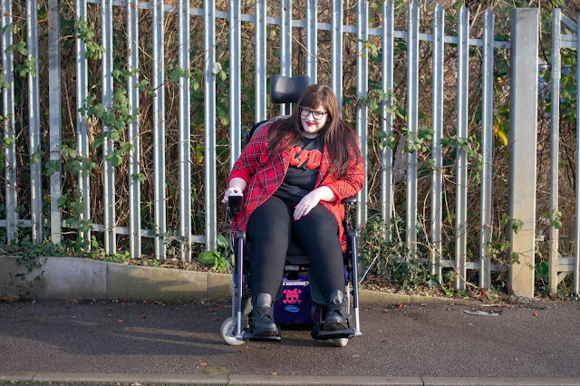 Plus size woman sat in powerchair wearing black jeans, ACDC tshirt, red tartan jacket and Doc Martens