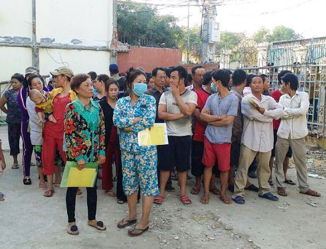 Vietnamese nationals stand together in Chbar Ampov district yesterday after they were detained by immigration officials. Photo supplied