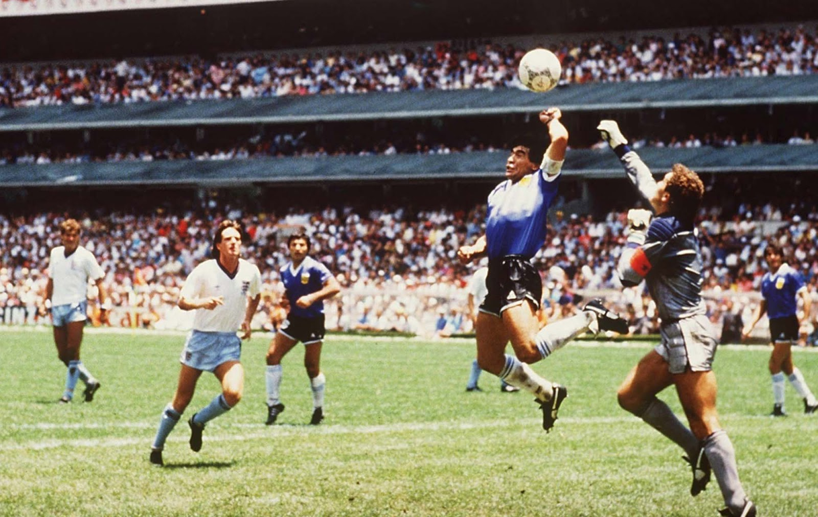 Diego Maradona uses his hand to find a way past England goalkeeper Peter Shilton to open the scoring. 1986.