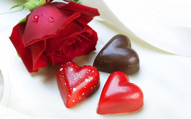 Chocolade in de vorm van liefdes hartjes en een rode roos