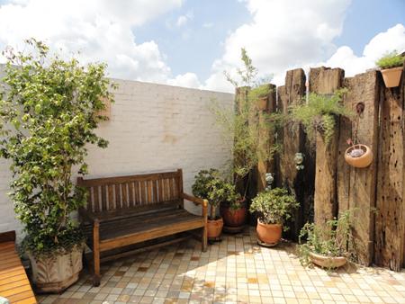 jardim com banco rústico e cerca rústica com vasos suspensos