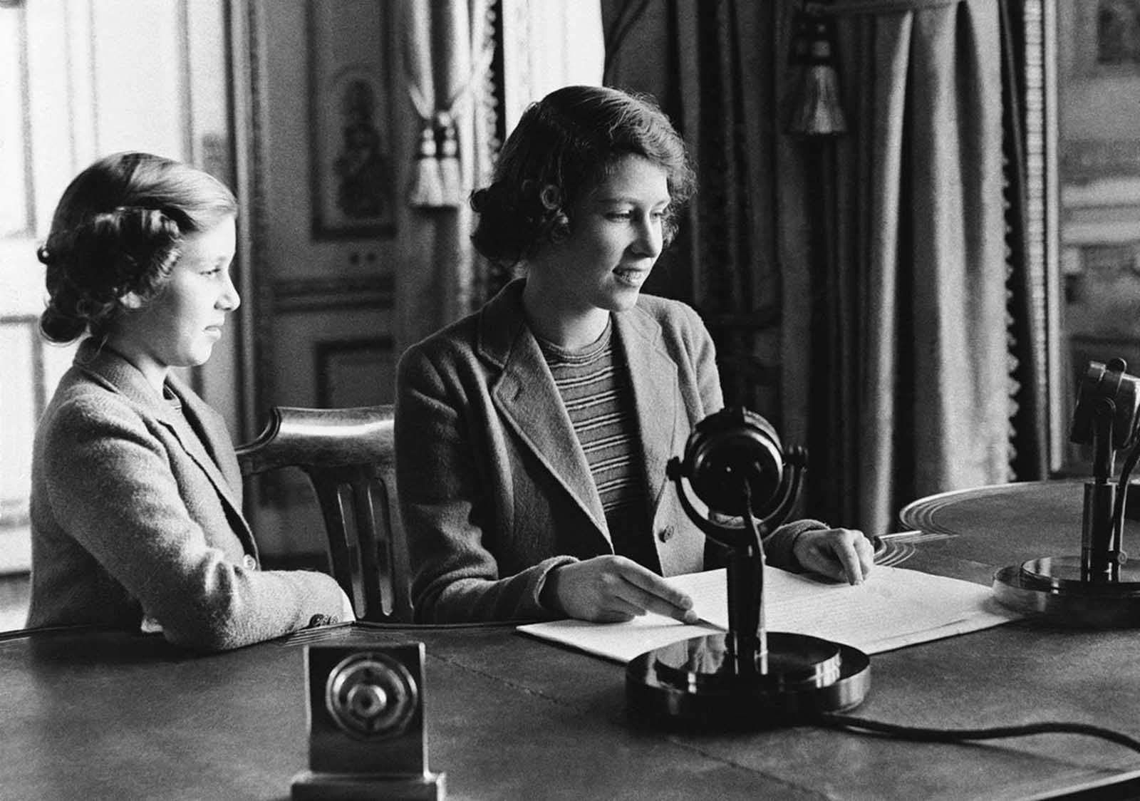 Princess Elizabeth of England (center), 14-year-old heiress apparent to the British throne, makes her broadcast debut, delivering a three-minute speech to British girls and boys evacuated overseas, on October 22, 1940, in London, England. She is joined in bidding good-night to her listeners by her sister, Princess Margaret Rose.