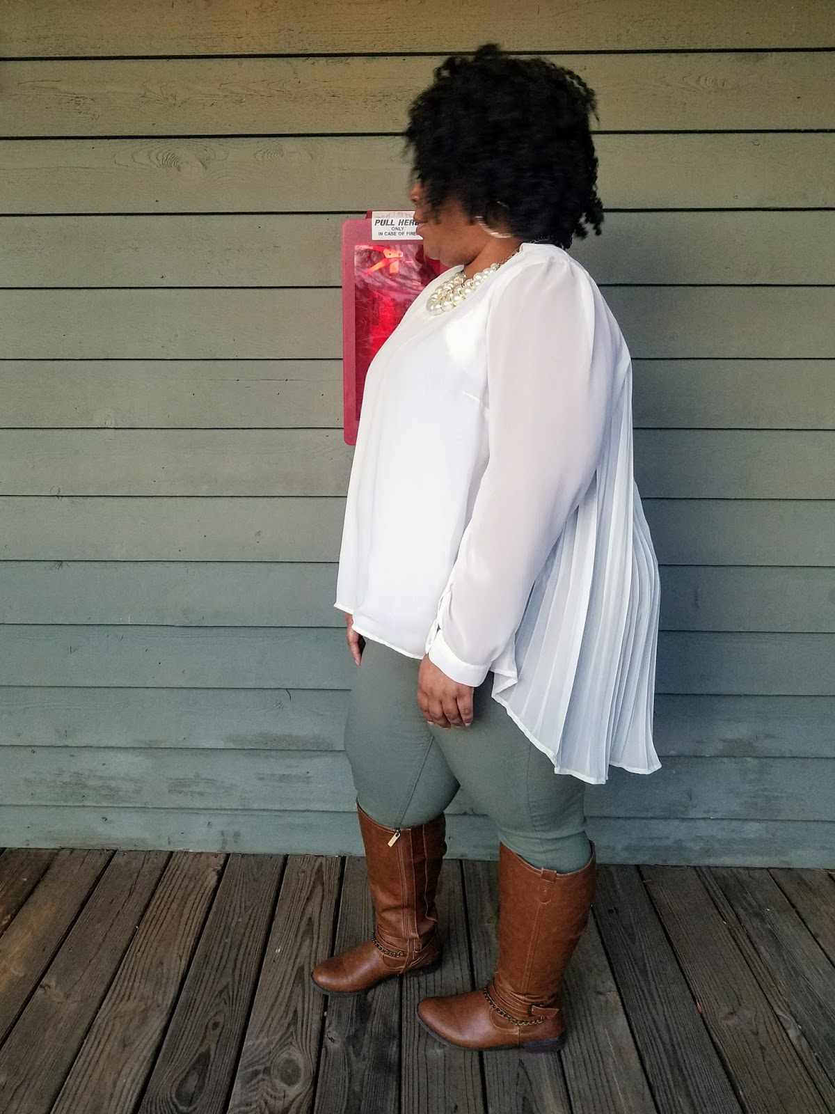 plus size, curvy model, flowy blouse, tall boots, jeggings, kinky natural hair, side pose