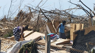 Photo of two women looking at the ruins of their houses blown away by the recent hurricane in Bahamas. Image source: BBC.com.