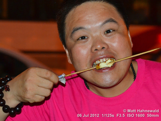 China, Beijing, Donghuamen night market, Chinese food delicacies, portrait, Chinese man eating from skewer