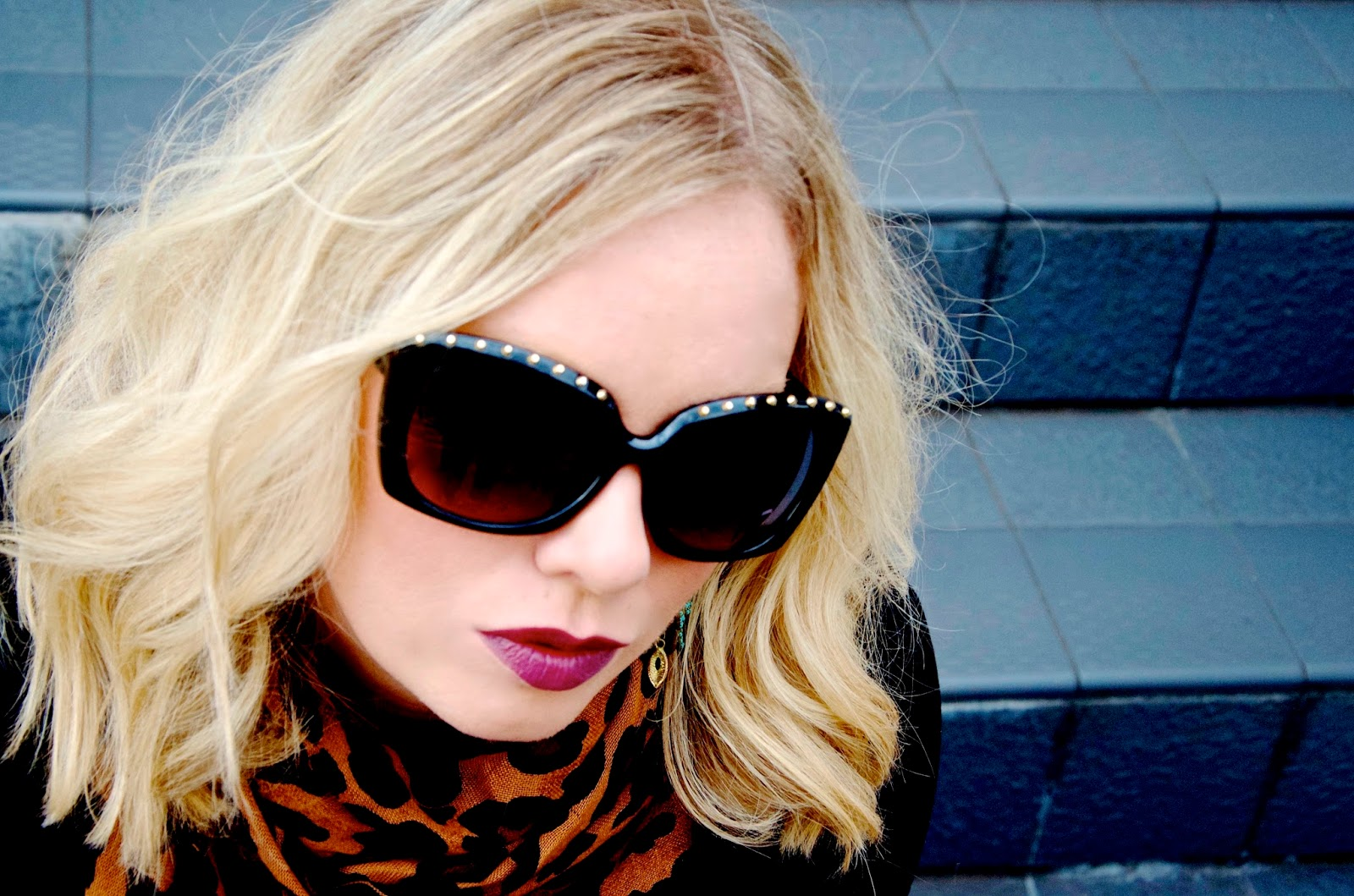 Gold studded black sunglasses, leopard print scarf, turquoise earrings and purple lipstick