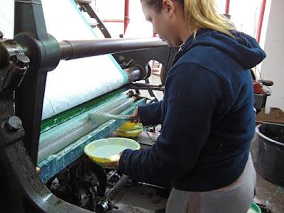 Kekfesto (blue dyed fabric), wax resist added to tray on machine