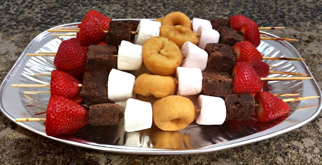 Lots of the sweet treat kebabs on a metal tray.