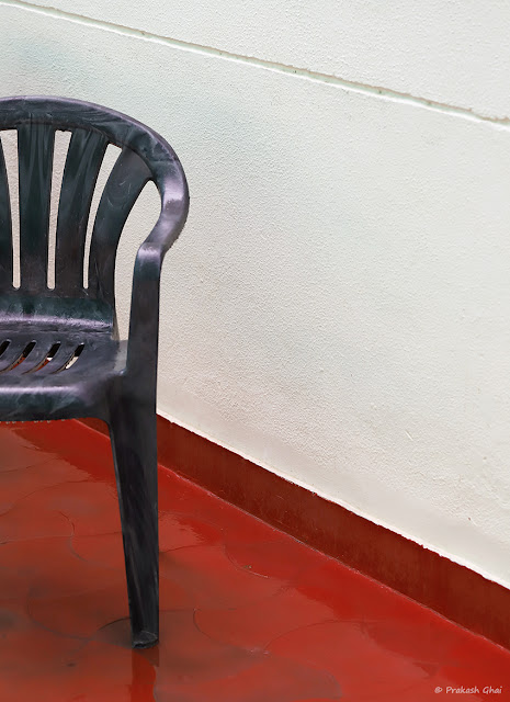 A Minimal Art Photo of A Plastic Chair against the White Wall at Jaipur Club Ltd.