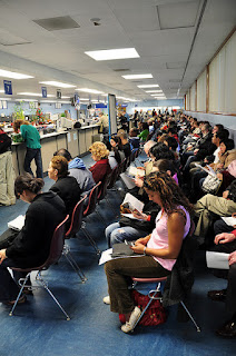 A busy DMV lobby filled with people waiting.