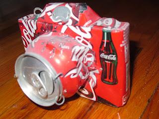 Camara fotográfica con latas de coca-cola recicladas.