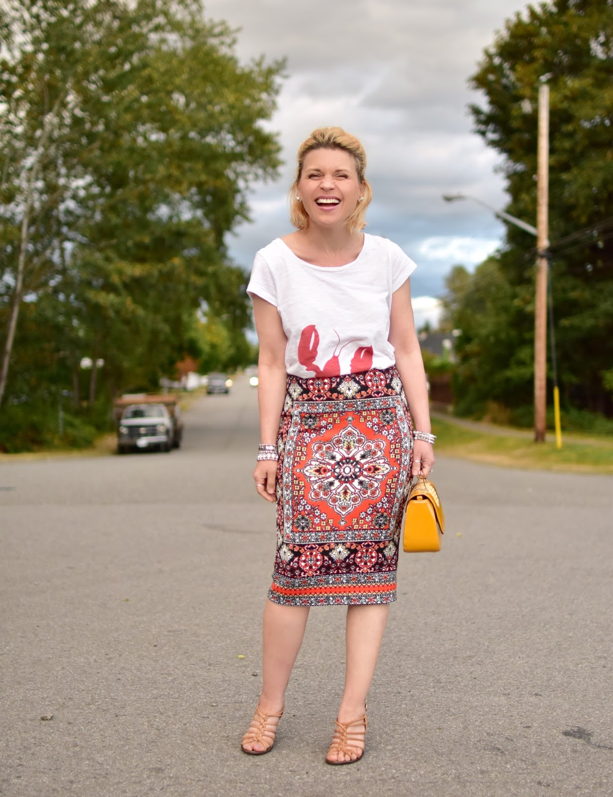 Monika Faulkner styles a lobster graphic tee with a patterned pencil skirt, strappy sandals, and yellow mini bag