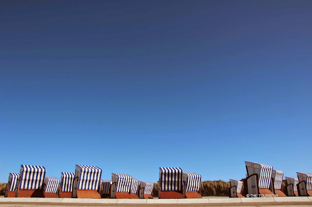 A group of 16 blue and white striped beach chairs under a bright blue sky.