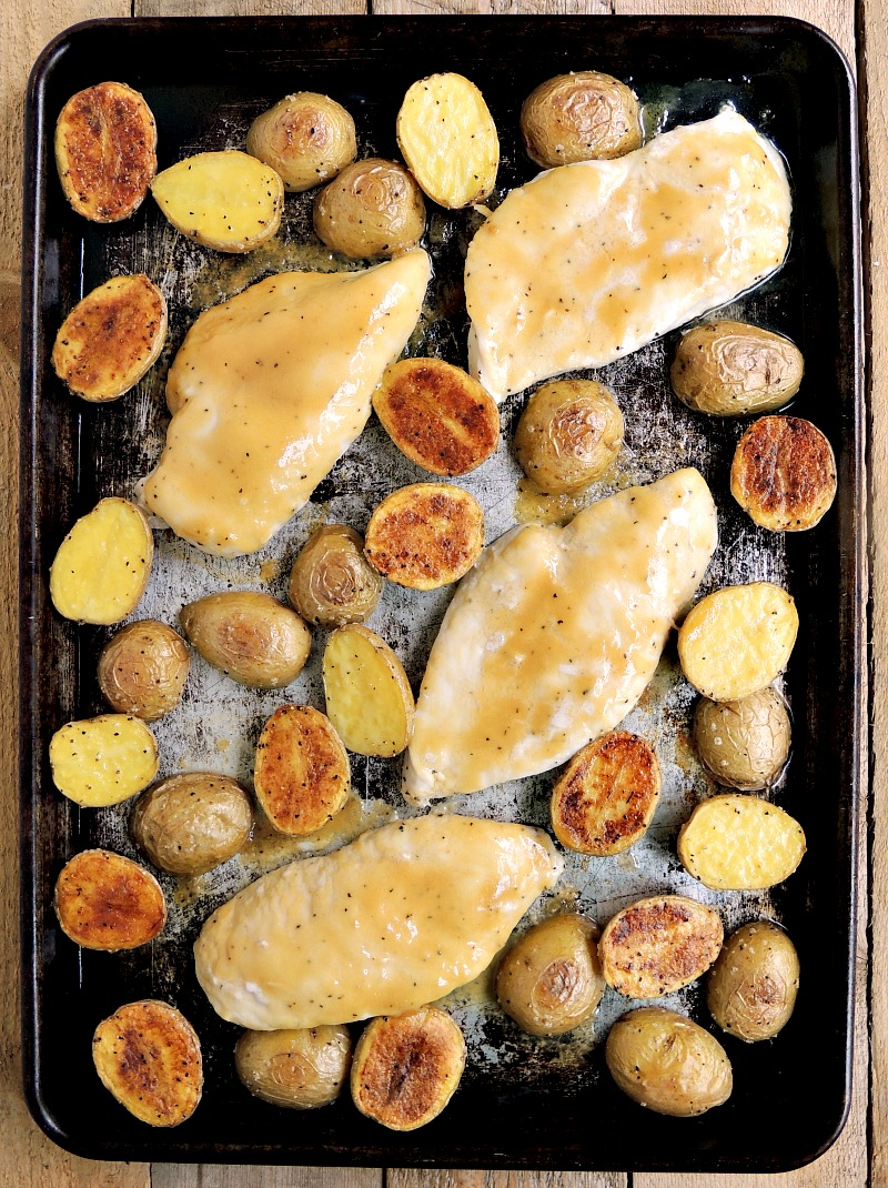 Honey mustard chicken and potatoes on a sheet pan.