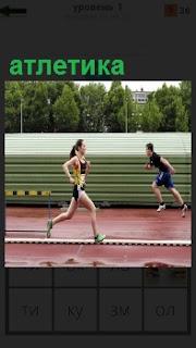 По спортивной дорожке бежит девушка и на соседней парень в обратную сторону в атлетике