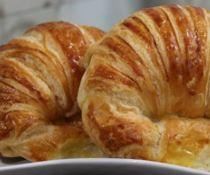 Imagem de croissant ou croaçã assado pronto para consumo.
