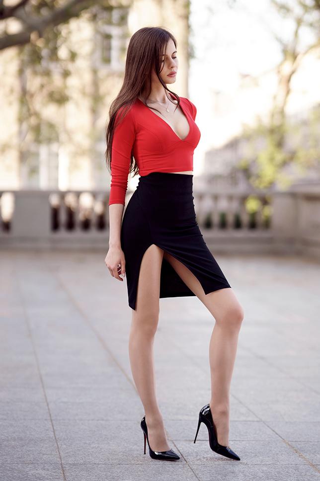 Czerwona bluzka z dekoltem, czarna spódniczka z rozcięciem z boku i cieliste rajstopy