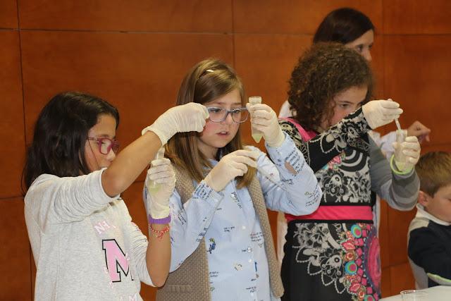 Niñas realizan experimentos en la feria de la ciencia