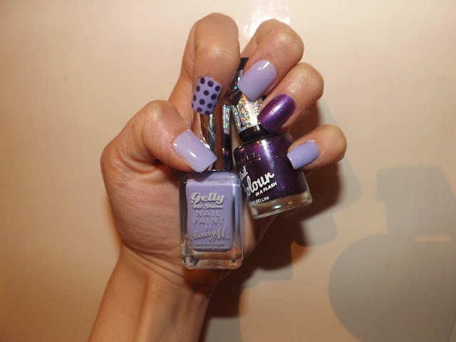 Hand holding purple nail polishes