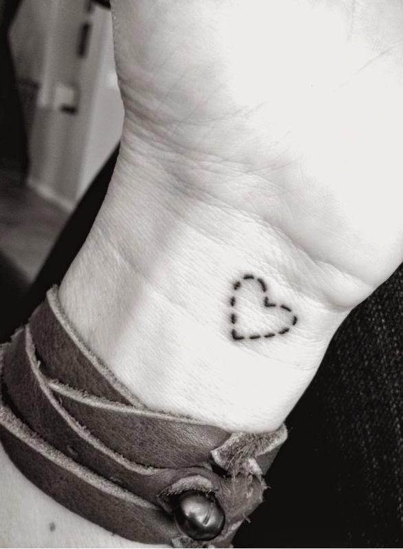 Chica con tatuaje pequeño en la muñeca de un corazon a puntitos