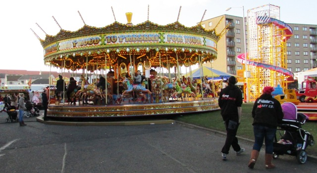 A carousel with children riding on it