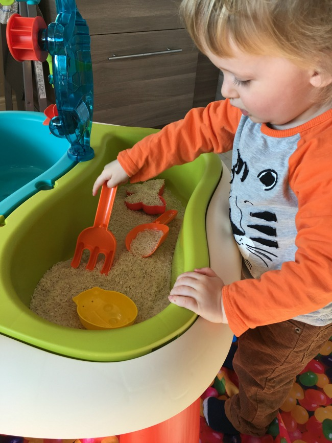 toddler playing with rice in the tray