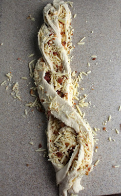 cheddar and bacon bread dough folded over itself in a loose braid