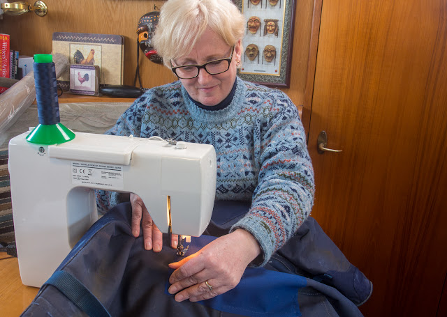 Photo of me sewing a patch on our torn flybridge cover