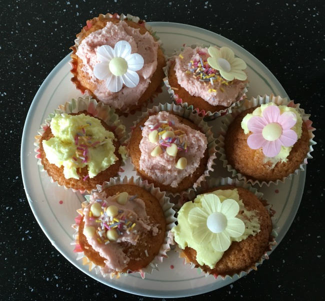 cup-cakes-on-a-plate-pink-and-yellow-icing-with-flowers-and-sprinkles
