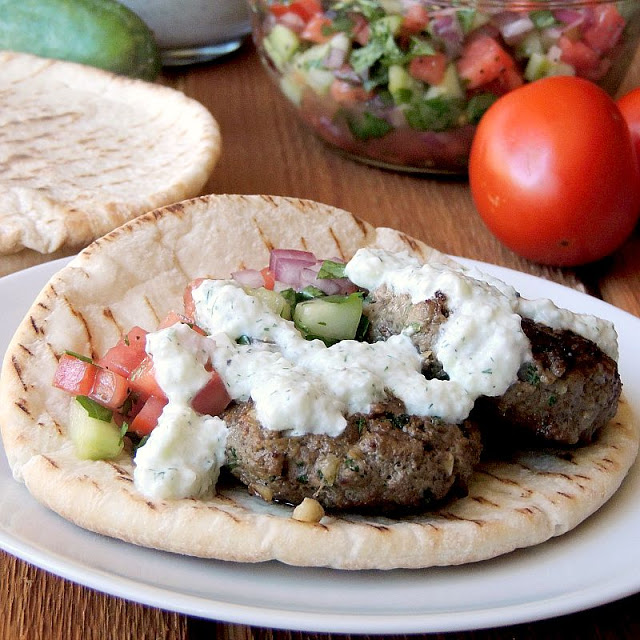 Beef Kofta with Tzatziki in a pita on a white plate with tomato and cucumber relish in a bowl behind it.