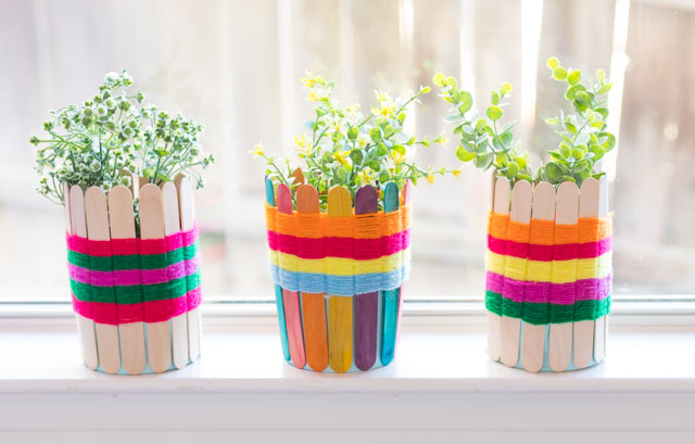 Use popsicle sticks and yarn to make these pretty woven baskets. Such a fun kids craft! #yarncrafts #kidscrafts #popsiclestickcrafts #popsiclestickweaving #kidsweaving