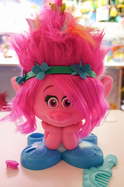 A pink troll with a big head and hair clips in her hair