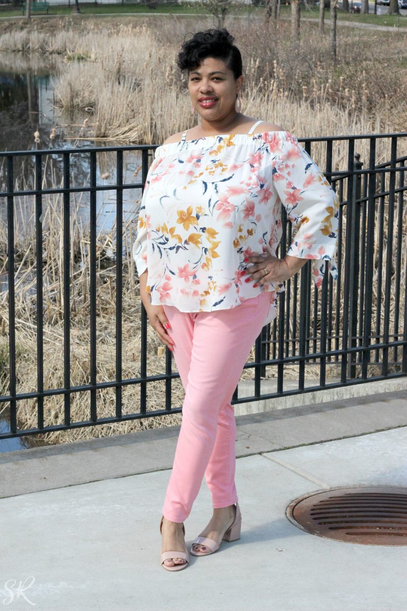 a woman wearing a floral off the shoulder blouse and pink jeans
