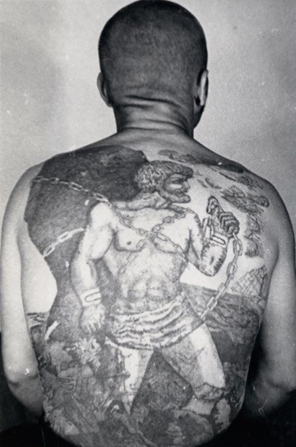 This tattoo is a variation on the myth of Pometheus, who, after tricking Zeus, is chained to a rock in eternal punishment. The sailing ship with white sails means the bearer does not engage in normal work; he is a traveling thief prone to escape.