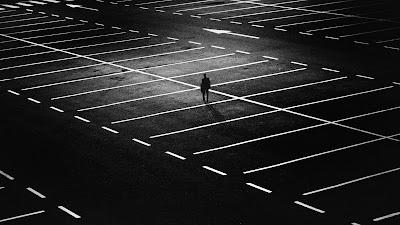imagen que muestra aparcamiento vacío de noche, con una persona sola vista de lejos. soledad y abandono
