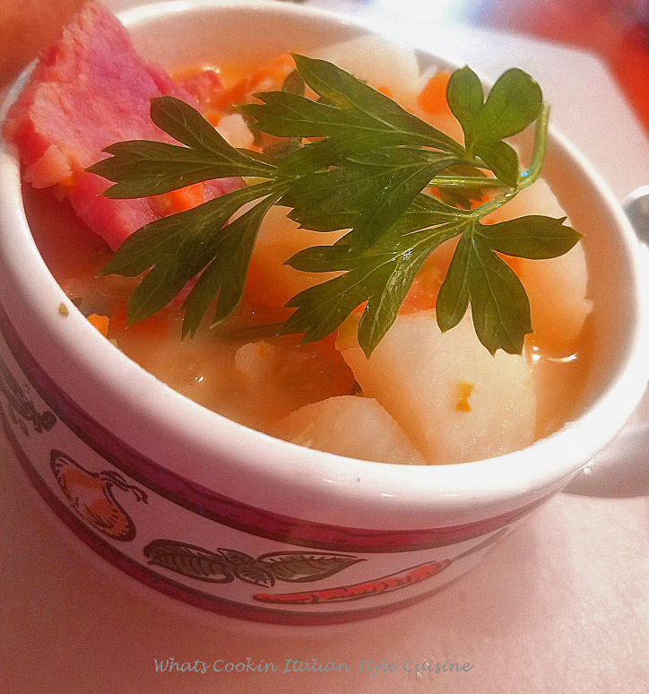 This is the easiest way to make potato soup added to this cup with fresh parsley on top. This soup is a potato soup with ham, it's a no fuss soup with vegetables ham and very low in calories. This potato soup has carrots, celery, ham all in a rich creamy broth made all in one pan. This is in a soup cup with vegetable design on it.
