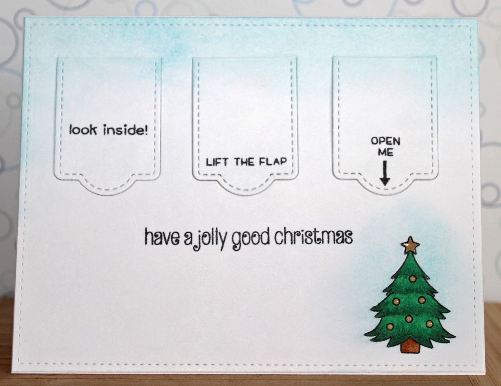 Theres a card for that happy holidays series peek a boo santa to begin i used the largest of my stitched rectangle dies by lawn fawn to cut out my front panel from 110lb copic friendly cardstock kristyandbryce Image collections