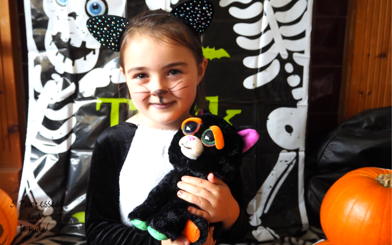 A young girl dressed in a black and white Halloween cat costume, with dimante cat ears and a face painted nose and drawn on whiskers holds a Feisty Pet Cranky Cathy, a 25cm soft toy, the toy is black with big doe eyes, cartoonish orange eyebrows, and a white mouth.
