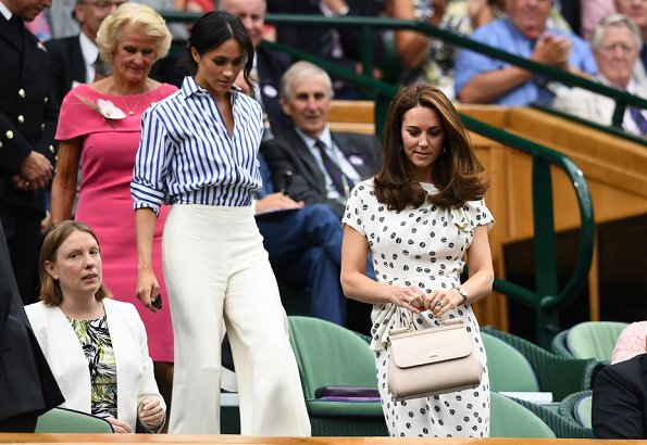 Kate Middleton wore a bespoke Jenny Packham dress. Meghan Markle wore Ralph Lauren Striped Cotton Shirt and Charmain Silk Wide leg Pant
