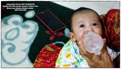 gambar bayi perempuan 2 bulan sedang diberi minum susu botol.